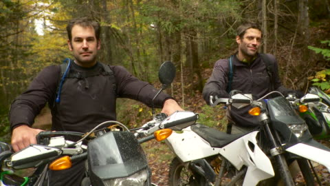 ms portrait of two men sitting on dirt bikes in forest / stowe, vermont, usa - male friendship stock videos & royalty-free footage
