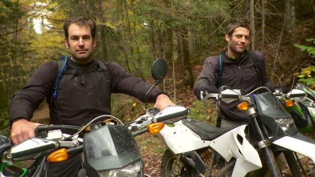 vídeos de stock, filmes e b-roll de ms portrait of two men sitting on dirt bikes in forest / stowe, vermont, usa - amizade masculina