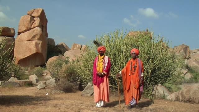 WS, Portrait of two Sadhus standing in rocky landscape, Hampi, Karnataka, India