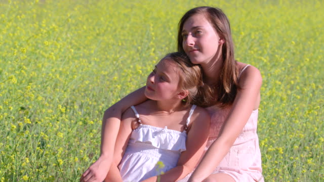 ms slo mo portrait of two sisters sitting in beautiful mustard field looking into distance pensively / thousand oaks, california, united states - mustard stock videos and b-roll footage