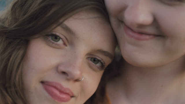 ECU SLO MO. Portrait of two sisters smiling at camera.