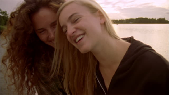 CU Portrait of two smiling and embracing women posing on pier at sunset, Ryd, Smaland, Sweden