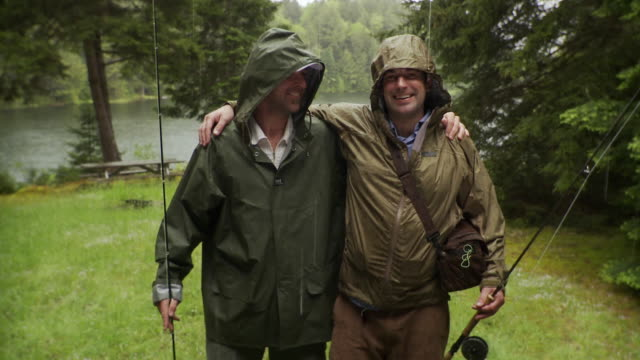vídeos de stock, filmes e b-roll de ms portrait of two smiling men with fishing rods standing in rain, lake in background, morristown, vermont, usa - amizade masculina