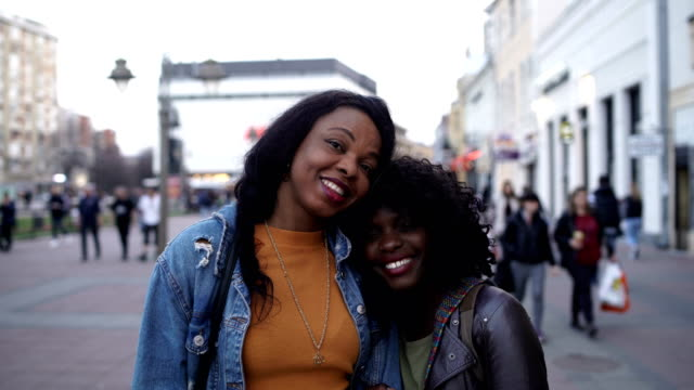 portrait of two smiling young  woman on the street-friendship and family concept - sister stock videos & royalty-free footage