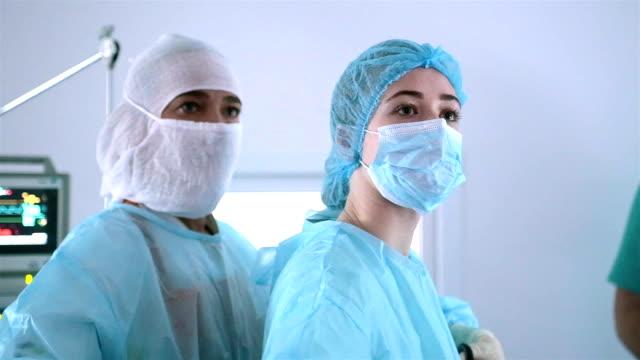 vídeos y material grabado en eventos de stock de retrato de dos cirujanos cirujanos durante la cirugía. - ayudante