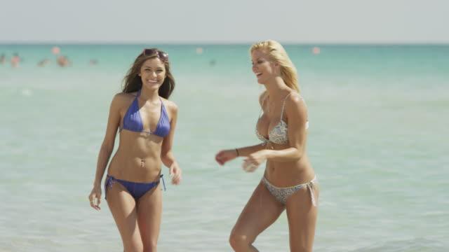 ms portrait of two women playing on beach / south beach, miami, florida, usa - サウスビーチ点の映像素材/bロール