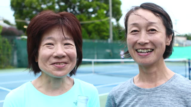 portrait of two women smiling on tennis court - 40代点の映像素材/bロール