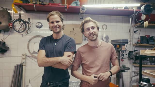 vidéos et rushes de verticale de deux jeunes concepteurs dans l'atelier - atelier d'artisan
