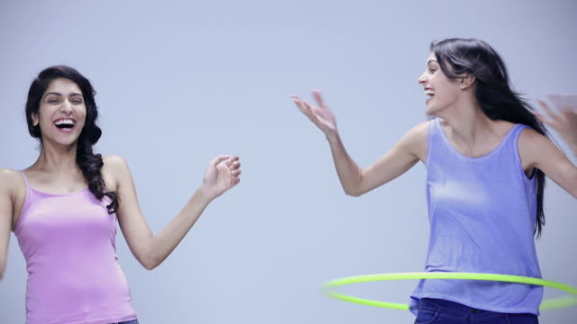 Portrait of two young women playing with hula hoop