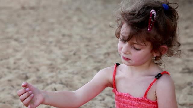 stockvideo's en b-roll-footage met portret van ongelukkig kind spelen met zand op het strand - tanden op elkaar klemmen
