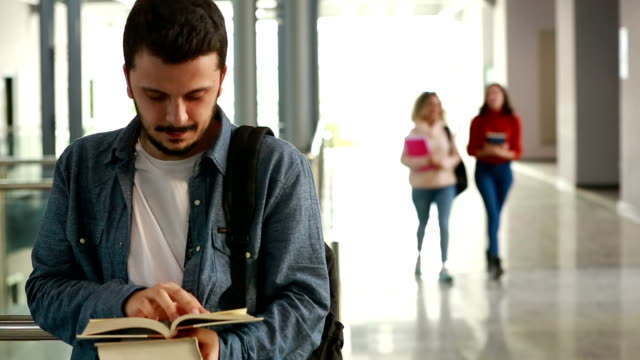 portrait of university student reading the book in corridor - part of a series stock videos & royalty-free footage