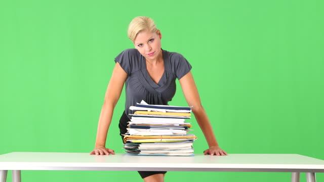 vídeos y material grabado en eventos de stock de portrait of very stressed businesswoman overwhelmed with large pile of work - three quarter length