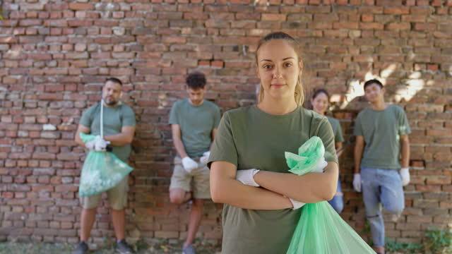 portrait of volunteer with garbage bag in front of volunteer team after environmental cleanup - gardening glove stock videos & royalty-free footage