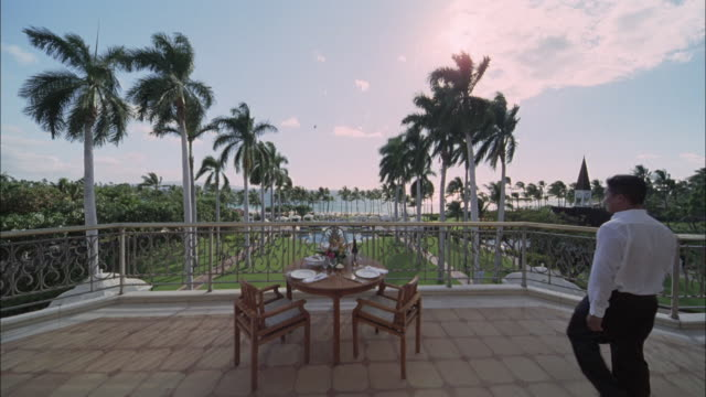 ds, ws, portrait of waiter at set table on terrace in luxurious resort, maui, hawaii, usa - fan palm tree stock videos & royalty-free footage