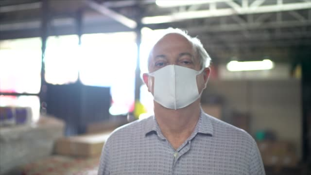 portrait of warehouse worker with face mask - e commerce stock videos & royalty-free footage