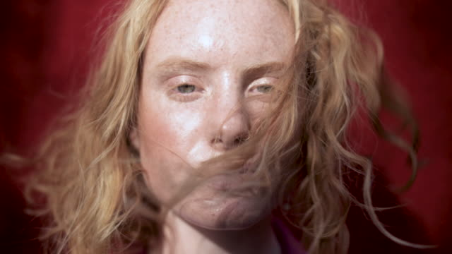 vidéos et rushes de portrait of wind blowing caucasian woman's hair, close up - wind