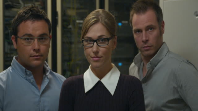 ms portrait of woman and two men, standing in server room, sydney, australia - female with group of males stock videos & royalty-free footage
