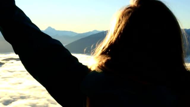 stockvideo's en b-roll-footage met portret van vrouw armen gestrekt op de bergtop - uitgestrekte armen