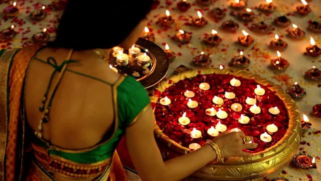 ms tu portrait of woman arranging diyas decoration in brass container during diwali festival - 盆点の映像素材/bロール