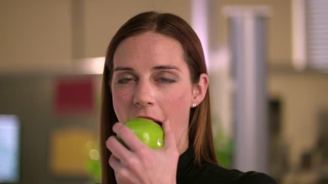 cu portrait of woman biting apple standing in office, appleton, wisconsin, usa - ウィスコンシン州アップルトン点の映像素材/bロール
