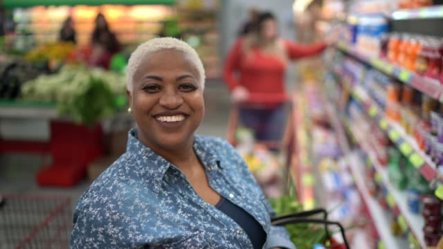 stockvideo's en b-roll-footage met portret van vrouw die bij supermarkt koopt - dairy product