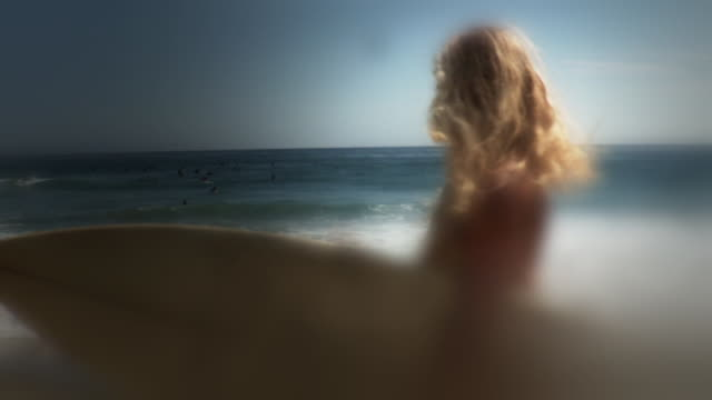 ms defocus portrait of woman carrying surfboard standing on beach, laguna beach, california, usa - kelly mason videos stock-videos und b-roll-filmmaterial