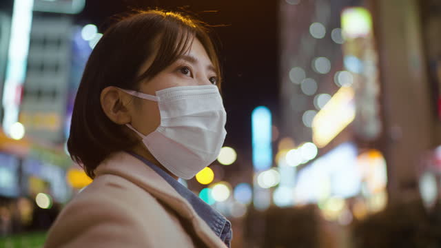 portrait of woman covering her face with protective face mask and looking away seriously in street in city - looking away stock videos & royalty-free footage