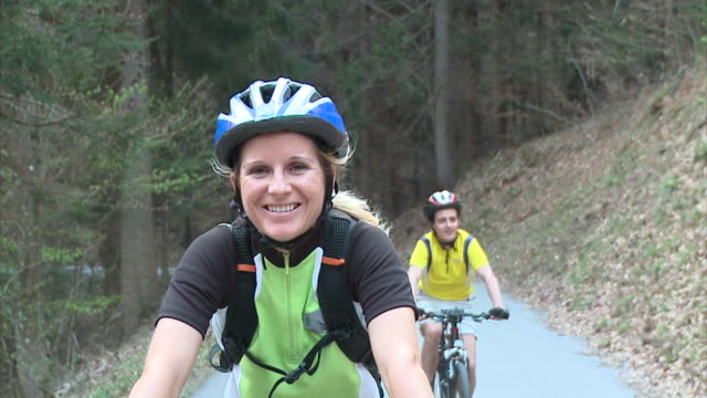 slo mo ms ds portrait of woman cycling in rural landscape, man in background, vrhnika, slovenia - vrhnika stock videos & royalty-free footage