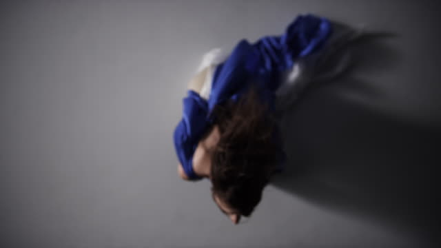 portrait of woman draped in blue silk fabric as she reaches up to camera
