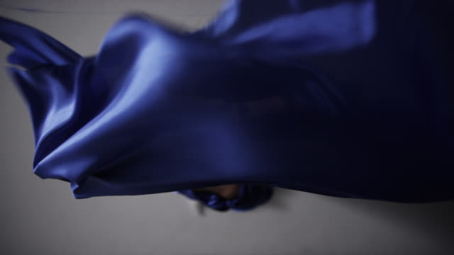 portrait of woman draped in blue silk fabric that floating around her in wind