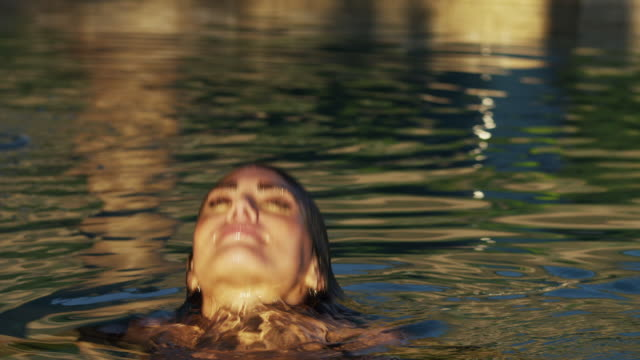 SLO MO MS Portrait of woman emerging from swimming pool / Cedar Hills, Utah, USA