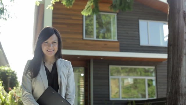 ms td portrait of woman holding clipboard standing in front of house / vancouver, british columbia, canada - estate agent stock videos & royalty-free footage