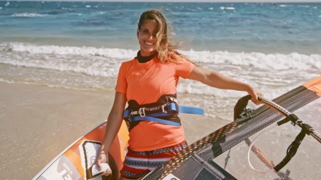 vídeos y material grabado en eventos de stock de retrato de mujer sosteniendo le windsurf en la playa soleada y sonriendo - windsurf
