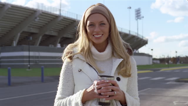 Portrait of woman holding travel mug at tailgate party outside football stadium