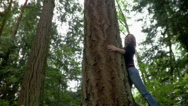 Portrait of woman hugging tree
