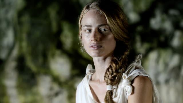 vidéos et rushes de portrait de femme dans une grotte - robe blanche