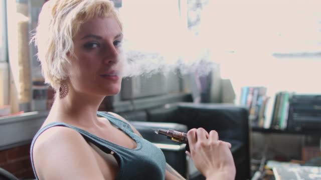 vídeos de stock, filmes e b-roll de retrato da mulher no apartamento fumando cigarro eletrônico - mulheres jovens