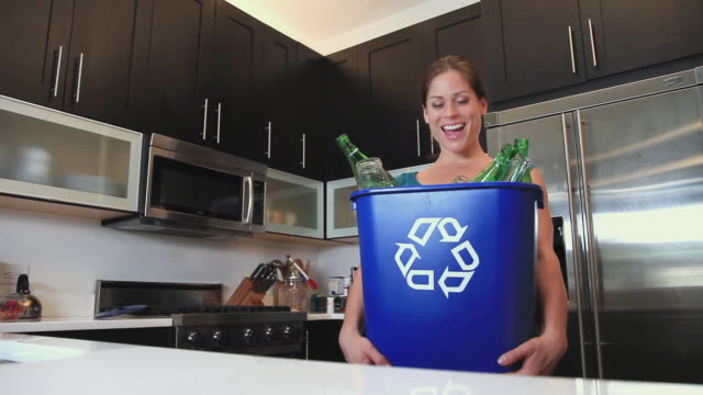 MS Portrait of woman in kitchen holding full recycling container, Hoboken, New Jersey, USA