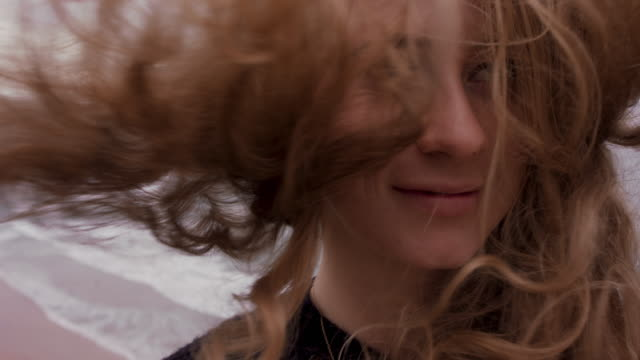vídeos de stock e filmes b-roll de portrait of woman in wind with curly blond hair blowing - hair