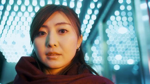 街の夜にネオン照明で照らされた女性の肖像画 - 真剣点の映像素材/bロール