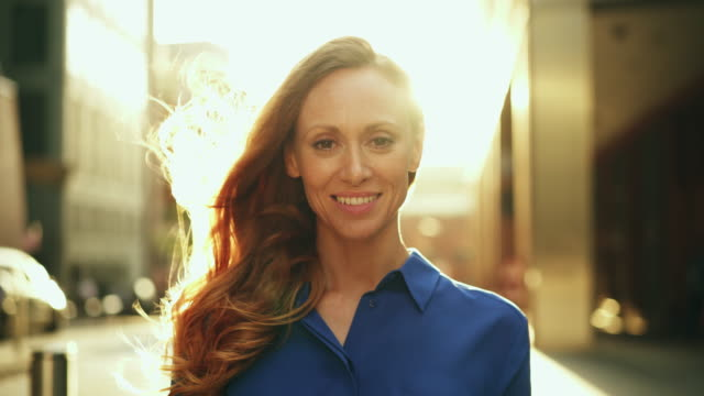 stockvideo's en b-roll-footage met portrait of woman looking at camera business, lens flare - tevreden