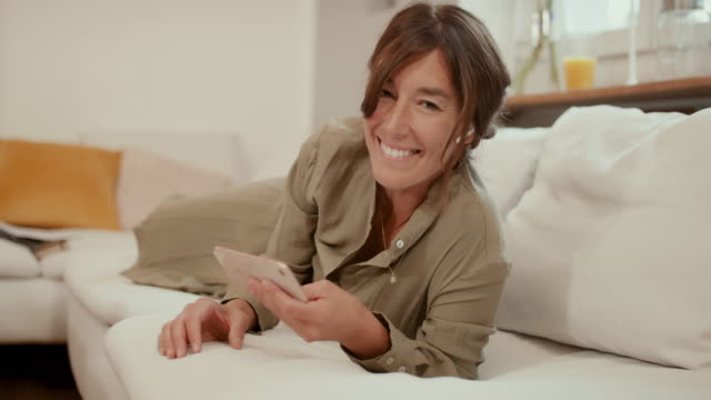 portrait of woman on sofa with smart phone smiling - quarantenne video stock e b–roll