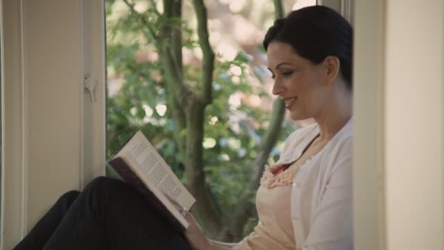 vídeos de stock e filmes b-roll de ms pan portrait of woman reading on porch / seattle, washington, usa - 40 44 anos