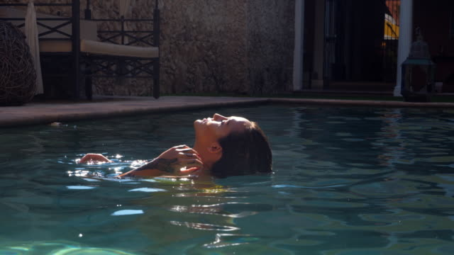 vidéos et rushes de ms portrait of woman relaxing in pool at outdoor spa - femme glamour