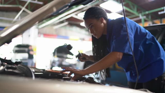 portrait of woman repairing a car in auto repair shop - bonnet stock videos & royalty-free footage