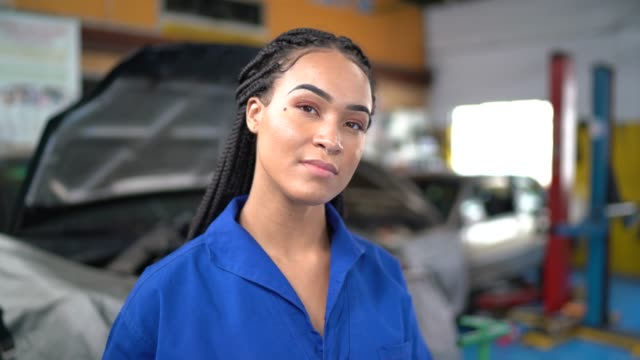 portrait of woman repairing a car in auto repair shop - jumpsuit stock videos & royalty-free footage