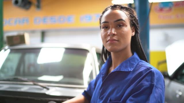 portrait of woman repairing a car in auto repair shop - laboratorio riparazioni video stock e b–roll