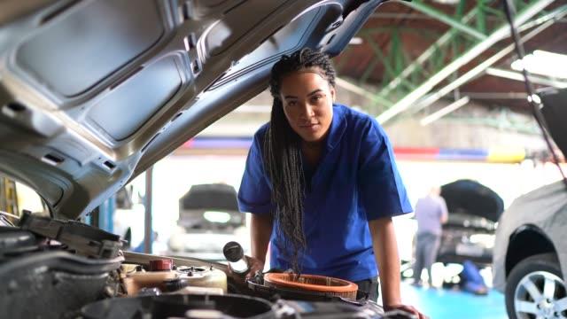 vídeos y material grabado en eventos de stock de retrato de mujer reparando un coche en el taller de reparación de automóviles - mecánico de coches