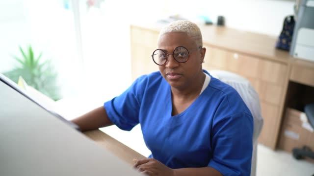 portrait of woman secretary at hospital reception - secretary stock videos & royalty-free footage