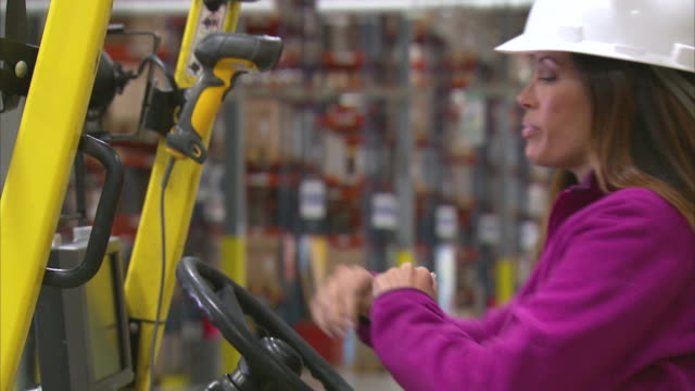 MS Portrait of woman sitting in forklift / LeBec, CA, United States